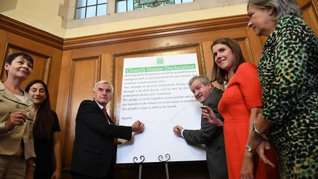 John McDonnell (centre left) and Ian Blackford, sign a declaration saying they will continue to meet