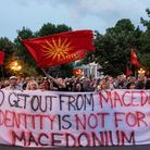 People wave flags and hold a banner with the lettering 'NATO get out from Macedonia, our identity is
