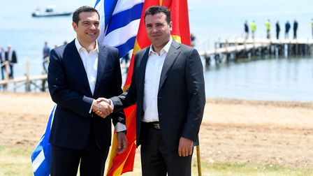 Macedonian Prime Minister Zoran Zaev (R) welcomes Greek Prime Minister Alexis Tsipras on the shore o