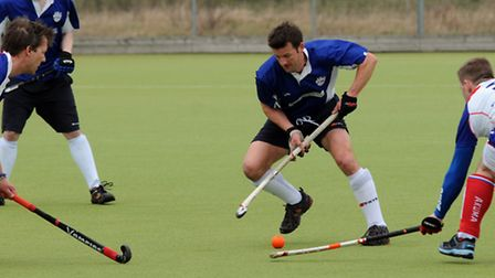 A Welwyn player skips between two Stortford players