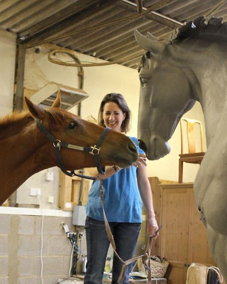 A horse comes face-to-face with the statue of Sefton while sculptor Camilla Le May watches