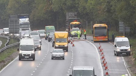 The burnt out bus sits on the hard shoulder as traffic enforcement officers clear up diesel spillage