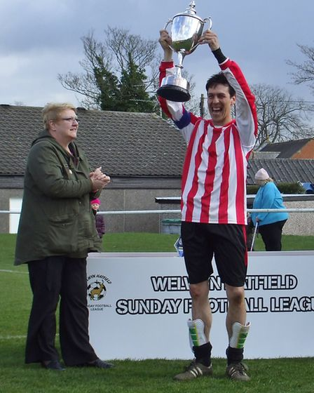 Chris Harris lifts the cup for Welwyn Rangers