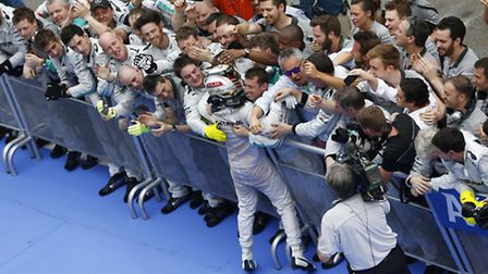 Formula One driver Lewis Hamilton is congratulated by his Mercedes colleague after winning the 2014