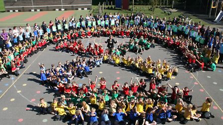The children making a windmill shape on the playground.
