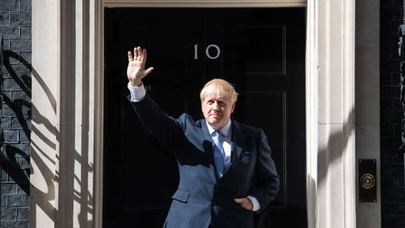 New Prime Minister Boris Johnson waves on the steps of 10 Downing Street, London, after meeting Quee
