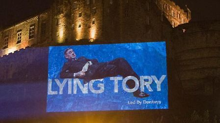 A projection of Jacob Rees-Mogg showing disregard for parliament is projected on to Edinburgh Castle