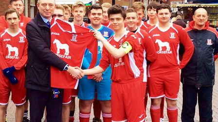 Centre manager, Kevin Smith, presents the new kit to Sam Bothamley, Wisbech Town Acorns' captain for