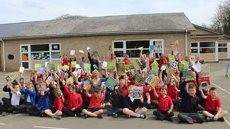 Hands up if you all love books: children at Peckover surround school principal Carrie Norman, one of