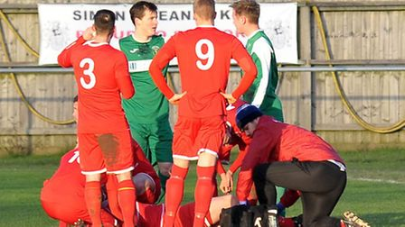 Wisbech Town's medical staff and players surround the injured Steven Reid. Picture: Steve Williams