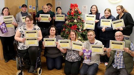 Some of Community House's volunteers and clients with special certificates recognising their achieve