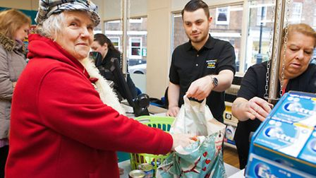 Poundland sales assistant Jordan Wool serves first customer Mary Killingsworth at the opening of the