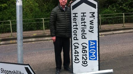 Clllr Malcolm Cowan with the road sign he reported broken on April 3.