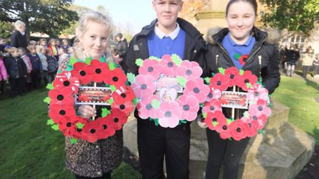 Year 6 children Megan Sparrow, Carter Terry and Cheyanne Barker ready to lay wreaths at the War Memo
