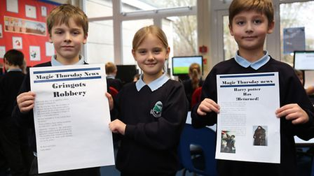 Commonswood School pupils Riley, 9, Lutzia, 8 and Tyler, 8 with their news stories.