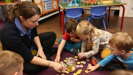 Nursery staff Charlie and Sammy with children in the new pre-school room at Busy Bees after the rece