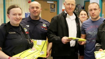 Rosmini Centre staff receiving high-visibility jackets from Wisbech firefighters. PHOTO: Cambridgesh