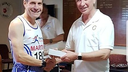 Martin Jennings receiving his prize for finishing third at the Deeping 10k.