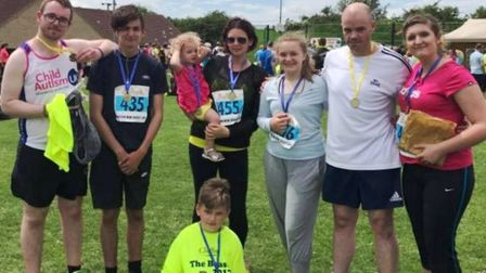 Megan Locks' family holding their medals after completing the Sutton Beast.