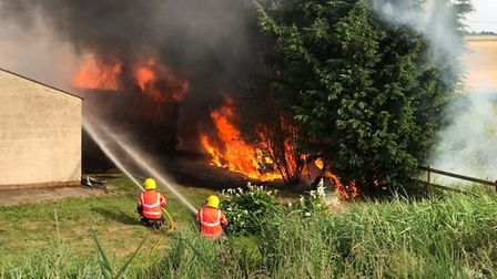 Cambs Fire crews prevented a blaze from spreading to a nearby house after an outbuilding cuaght fire