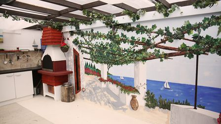 Arty Achilleos decorated his garden to look like a holiday destination because he couldn't afford to