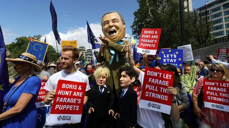A model of Nigel Farage carrying puppets of Boris Johnson and Jeremy Hunt, with pro-European Union s