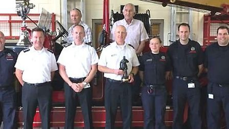 Phil Pilbeam with officers and crew members past and present in front of vintage fire engine Vivien.