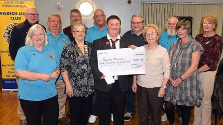 Members of Wisbech Lions Club give a £500 cheque to Jacob Moore so he can buy a new iPad to communic