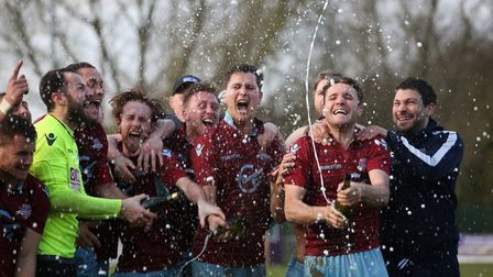 Welwyn Garden City F.C. players and staff celebrate with champagne after winning the league with a l