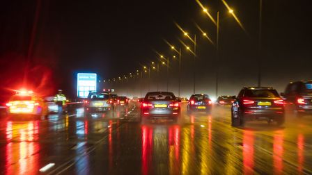 Motion blurred photograph of traffic at in night in the rain on a British motorway with police offic
