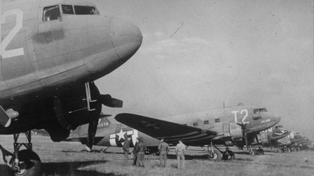 C-47 Skytrains of the 437th Troop Carrier Group, lined up before a mission, bearing white invasion s