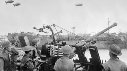 A Bofors gun crew stand watch for enemy aircraft while Landing Ship Tanks are loaded at a south coas