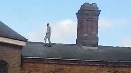 The two men caught on camera dangerously climbing up and sliding down rooftops in Wisbech. Picture: