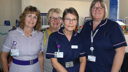 Four midwifery staff are hanging up their uniforms after delivering thousands of babies and giving a