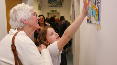 Digswell Primary School year six pupils stand with their artwork which is on display at Digswell Art