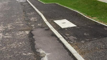 "Unadopted housing estate Cromwell Gardens in Wisbech with hazardous pavements, potholes and a ""dumpi"