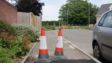 """Unadopted housing estate Cromwell Gardens in Wisbech with hazardous pavements, potholes and a """"dumpi"""