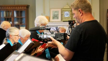 Film captures the stories of migrants in Fenland: Jake Bowers filming the singers. Picture: PETER KI