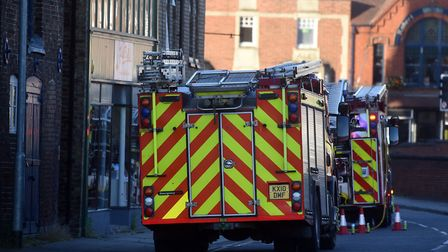 Arsonists set fire to a large amount of rubbish which caused a blaze that spread to trees and a near