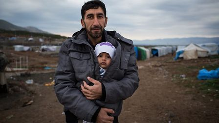 A Syrian refugee holds his young son in a refugee camp in northern Iraq. Credit: Andrew McConnell