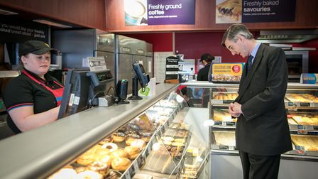 Jacob Rees-Mogg stops to buy a sandwich as he walks along the main street near his constituency offi