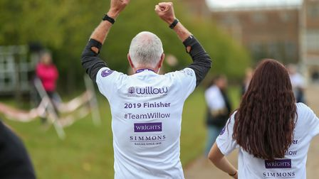 A finisher celebrates completing the Willow 10K run at Hatfield House. Picture: DANNY LOO