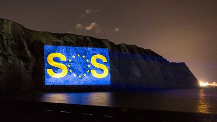 A giant SOS message is projected on to the white cliffs of Dover. Photograph: Led By Donkeys.