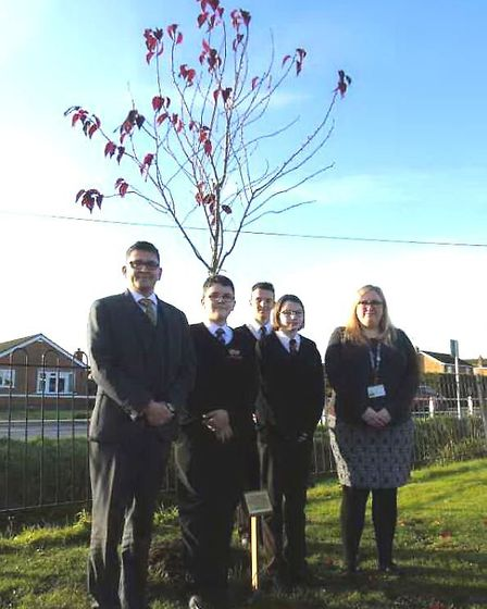 The head, teachers and pupils at Marshland High School with their cherry tree which was planted to r