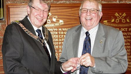 Incoming chairman Michael Bates (left) presented a past chairman's badge to the outgoing John Groom.