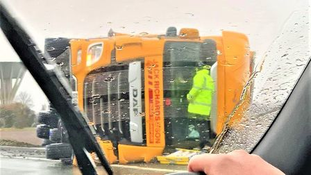 Pictures show a large lorry on its side in the wet windy weather at Gedney roundabout along the A17.