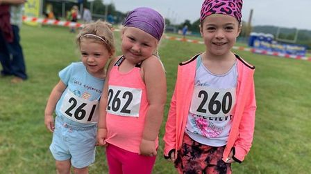 Isla Newsome (centre) along with cousins Flo and Bella are running one kilometre every day around th