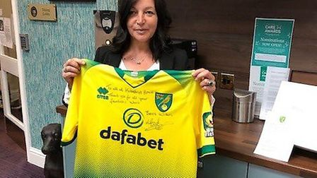 Paula Colman, acting general manager at Hickathrift House, holds a Norwich City FC shirt. Picture: S