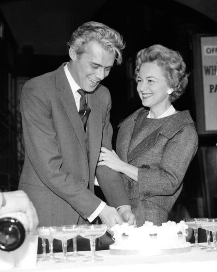 Film star Dirk Bogarde cuts his birthday cake, watched by co-star Olivia de Havilland, on the set of