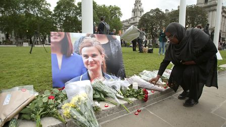 A woman lays some flowers at Parliament Square opposite the Palace of Westminster, central London, i